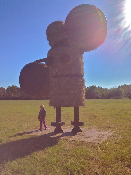 Little Girl in a field near hay sculpture